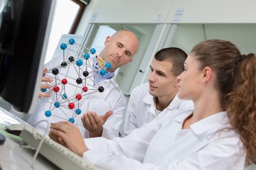 smiling scientists working with dna model in laboratory