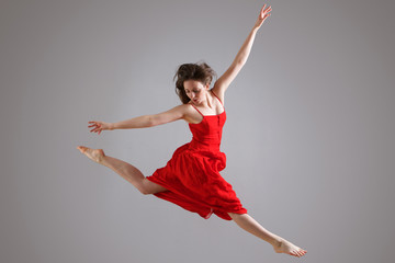 elegant dancer in red dress jumping against gray background