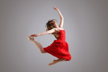 elegant female dancer in red dress jumping in the air