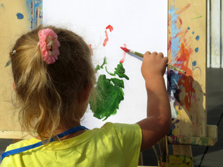 A little girl paints with a brush on the easel, back view. Concept for talented child, creativity of children, art school