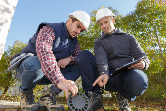 worker and manager inspecting sewer drain