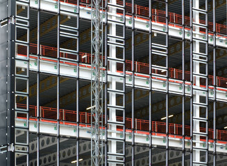 view of a large building development under construction with steel framework and girders supporting the metal floors with safety fences and hoists