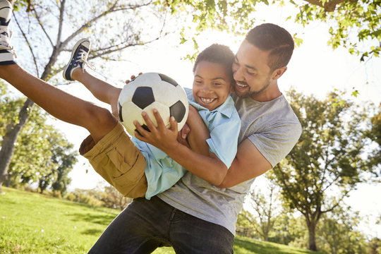 Father And Son Playing Soccer In Park Together