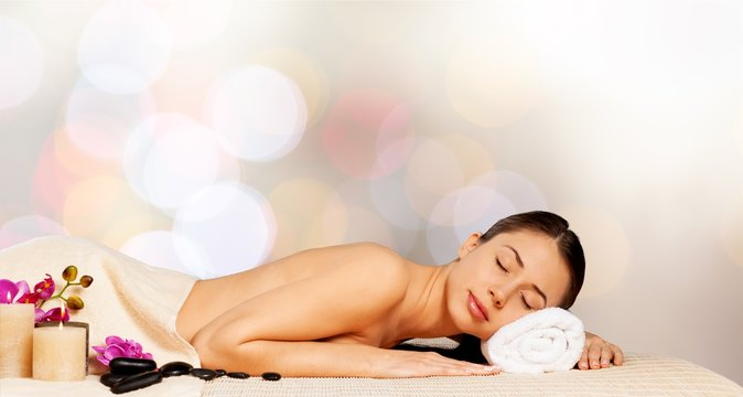 Beautiful young woman relaxing with stone massage at beauty spa