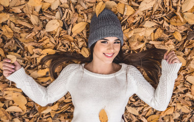 Enjoying autumn. Top view of beautiful young woman lies on autumn leaves and looking at camera.