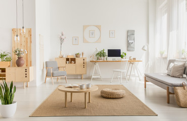 Real photo of a modern home office interior with wooden furniture, coffee table, sofa, pouf and computer on a desk