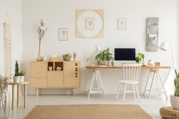 Real photo of a simple home office interior with a cabinet, flower, graphics and desk with a computer. Place your graphic