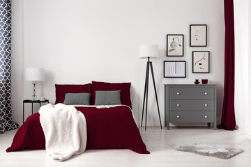 Real photo of a glamour bedroom interior with dark red bed, blanket, lamp and grey commode. Empty wall, place your painting