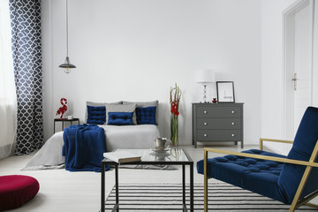 Real photo of a modern bedroom interior with a bed, commode, flower, coffee table, armchair and blue accents. Empty wall, place your painting