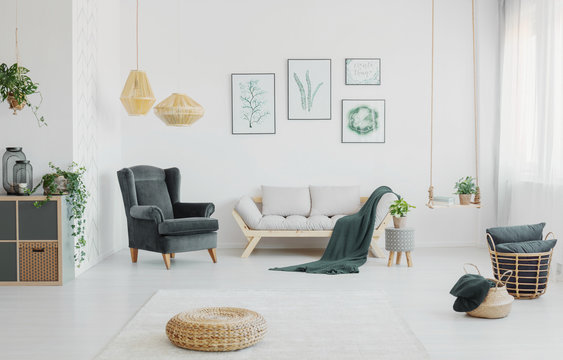 Wicker pouf in a spacious living room interior with a armchair, sofa, posters and pillows in a basket. Real photo