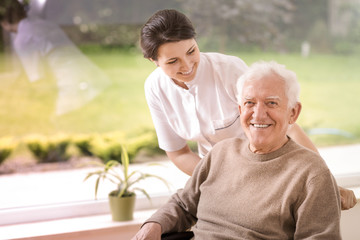 Friendly nurse supporting disabled smiling elderly man in the nursing house