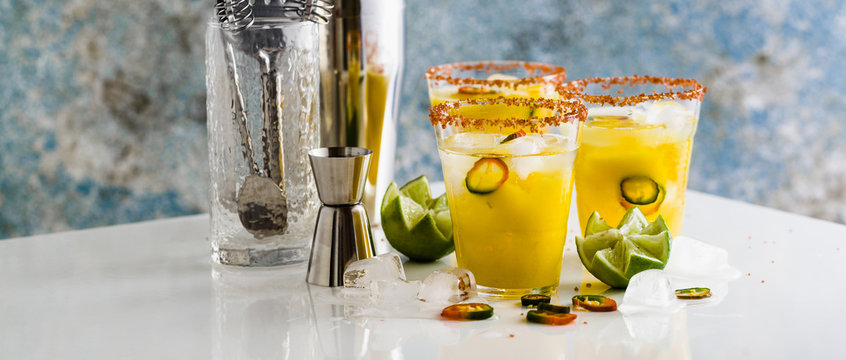 banner of cocktail margarita of tequila, mango juice, hot pepper and lime on the table. bar accessories