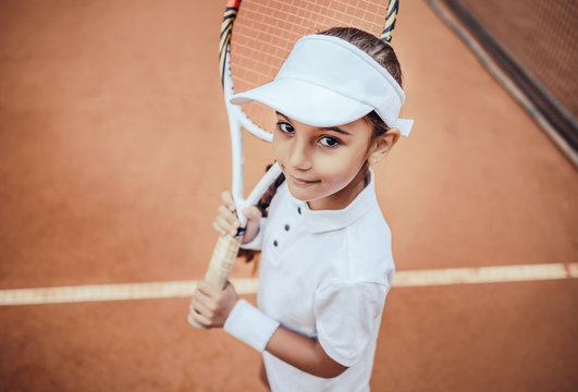Tennis is my favorite game! Portrait of a pretty sporty child with a tennis racket. Little girl smiling at camera on tennis court. Training for young kid.