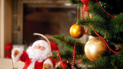 Closeup image of golden baubles hanging on Christmas tree branches