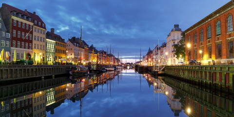 Panorama of Nyhavn with colorful facades of old houses and old ships in the Old Town of Copenhagen, capital of Denmark.