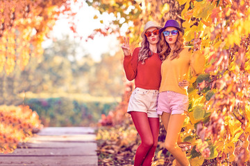 Fall Fashion. Two Young Amazing Woman in Colorful Park with Kiss Face and peace sign. Lovable Girl Friends Fooling Around Enjoy Nature. Urban Outdoor. Model in Stylish Trendy Autumn Outfit
