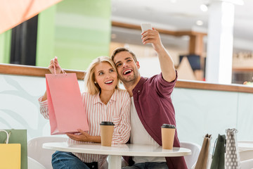 man taking selfie with girlfriend showing shopping bag at table with disposable cups of coffee in cafe