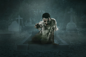 Horrible male zombie crawls out of the grave