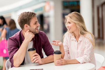 happy woman with paper cup of coffee gesturing by hand and talking to boyfriend at table in cafe