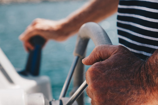 Close-up view of a Senior Man hands driving a little boat - Captain
