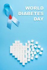 inscription world diabetes day, blue ribbon awareness with red blood drop, broken heart of sugar cubes, blue background