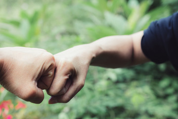 closeup hand of person team work fist bump in nature background.