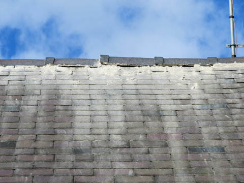 Shoddy roofing work by cowboy builder. Results of rouge worker posing as skilled tradesman. Badly pointed ridge tiles on slate roof, mortar running down tiles. Close up.