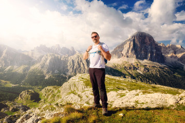 Nestled in the beautiful alpine scenery, a man admires the high-altitude landscape with mountain peaks and cloudy skies.