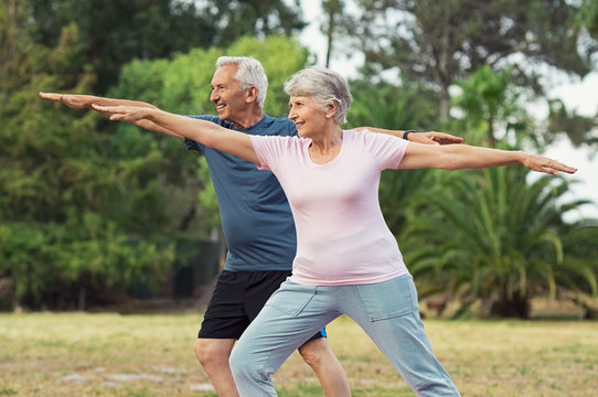 Old man and woman doing stretching exercise