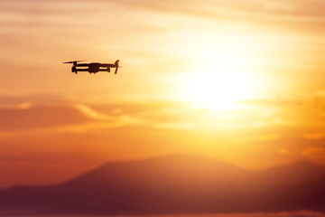 The drone with cinema camera flying over the misty mountains at sunset