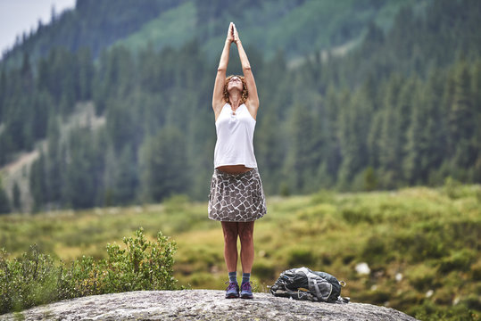 a young woman with curly hair doing yoga on top of a giant boulder in the mountains