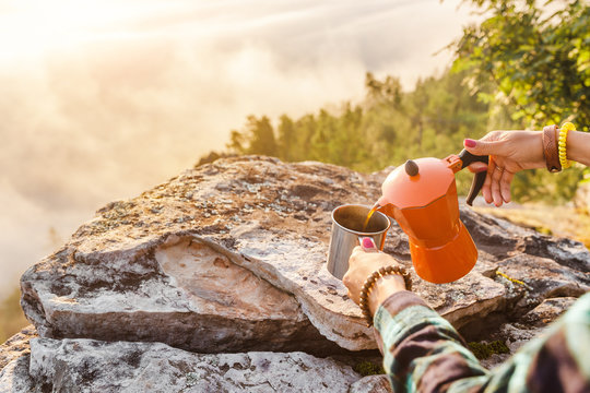 coffeepot and coffee in cup near camping site at foggy mountains background
