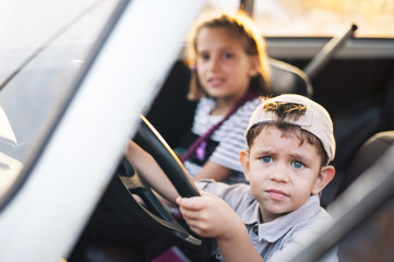 The little guy sits in an old car with a serious face and holds the wheel in the sunset. A young girl sits next to him and smiles
