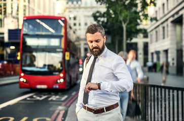 Hipster businessman waiting for the bus in London, checking the time.