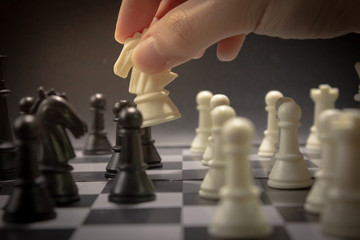 White and black chess battle on chess board knight move.