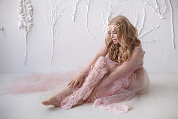 Delicate portrait of a young model girl. The image of the bride, a light lace dress in pink, a beautiful hairstyle and a natural make-up. Light photo studio, natural light from the window.