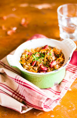 Traditional polish food. Bigos, stewed cabbage with carrot, onion, green lentil and pork meat sausages in a pot on a wooden table, selective focus. German cuisine. Comfort food.