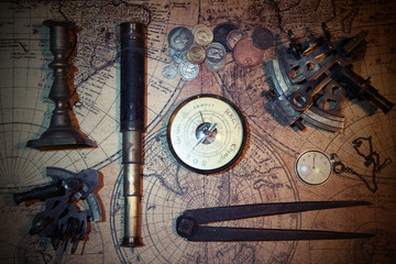 Ship lantern, compass, old coins and sextants. Travel and marine engraving background.Pirate map. Retro style.