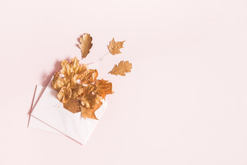 Autumn composition. Envelope with golden leaves on pastel pink background. Autumn, fall concept. Flat lay, top view, copy space