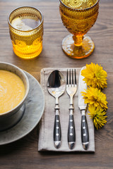 Rustic table setting with pumpkin soup, linen napkin, cutlery, ceramic plates, yellow glasses and yellow flowers