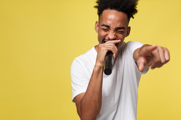 Stylish afro american man singing into microphone isolated on a yellow gold background Fotobehang