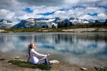 Woman on the lake shore meditating and relaxing. Beautiful view of mountains and reflections in the lake. Alpine meadows in Garibaldi Park near Whistler. British Columbia. Canada.