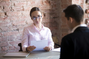 Serious HR young manager woman interviewing male in the office. Suspicious female holding curriculum vitae and looking at candidate, man sitting back to camera. Bad first Impression, failed interview