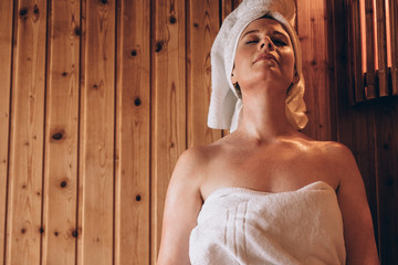 Woman sitting in a wooden spa with eyes closed.