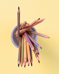 colored pencils isolated on yellow background