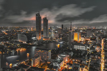 Bangkok night life with glow in the dark color tone, illuminated cityscape on skyscraper