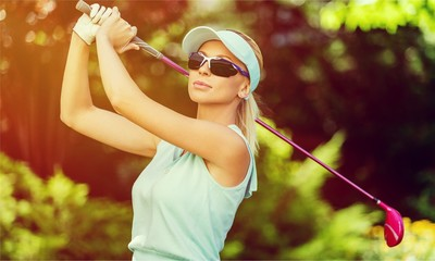 Young happy Caucasian woman with golf club over  background.