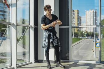 Young man standing next to big windows and looking at watches at metro station.