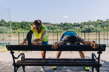 Happy couple stretching together beside park. Stay fit concept urban.