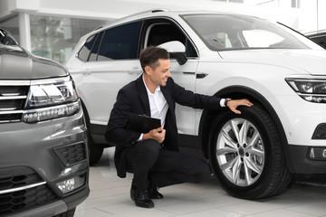 Salesman with clipboard near new car in salon